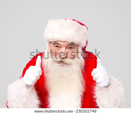 Santa claus gesturing thumbs up against grey - stock photo