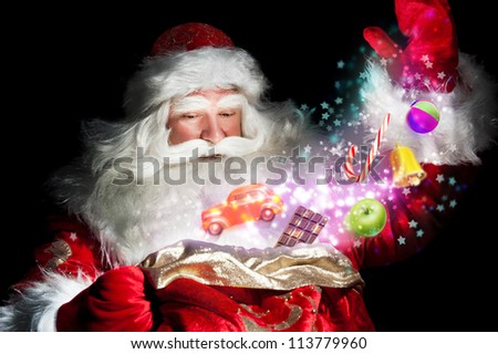 Santa Claus getting gifts and confection from his bag and showing miracle - stock photo