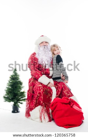 Santa Claus gives gifts to the pretty little girl