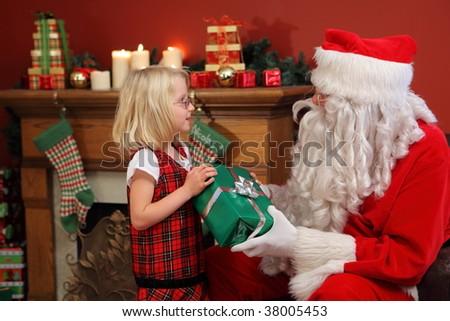 Santa Claus gives young girl Christmas gift - stock photo