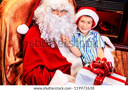 Santa Claus giving a present to a little cute boy near the fireplace and Christmas tree at home. - stock photo