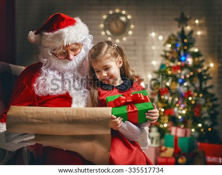 Santa Claus giving a present to a little cute girl - stock photo