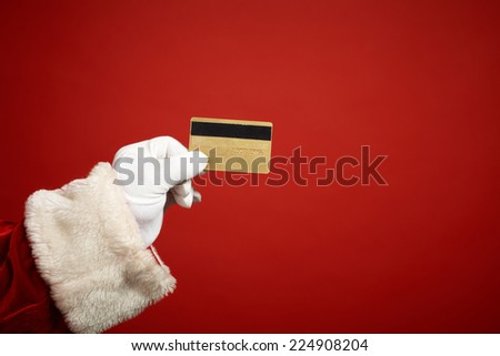 Santa Claus gloved hand holding plastic card - stock photo