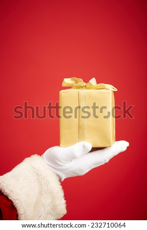 Santa Claus gloved hand with golden giftbox - stock photo