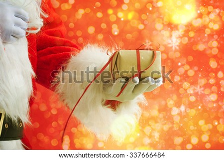 Santa Claus gloved hands holding gift box - stock photo