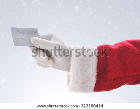 Santa Claus hand holding a platinum credit card over a snowy background. Great for shopping concept, lay-away, or consumerism.