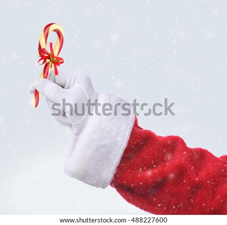 Santa Claus hand holding an Old Fashioned Candy Cane with a ribbon and bells. Hand and arm only with snow effect.