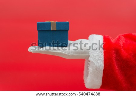 Santa Claus hand holding Christmas Gift box over red background