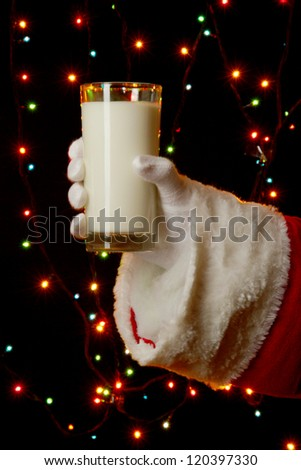 Santa Claus hand holding glass of milk on bright background - stock photo