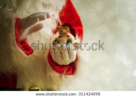 Santa Claus hand holding toy bear