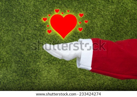 Santa Claus hand in white glove holding  little hearts surrounding a big heart isolated on green background.