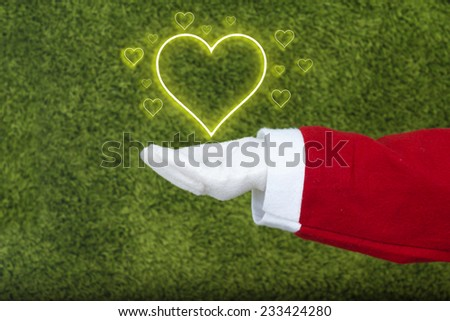 Santa Claus hand in white glove holding  little hearts surrounding a big heart isolated on green background. - stock photo