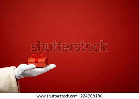 Santa Claus hand in white glove holding small red giftbox in isolation - stock photo