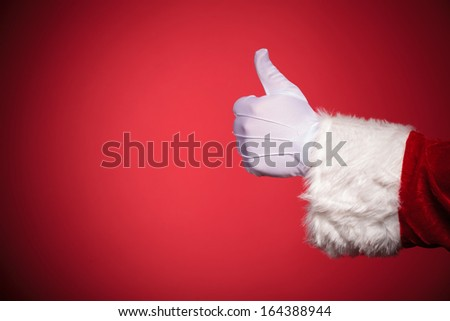 Santa Claus hand showing thumbs up ok sign over red background with copy space - stock photo