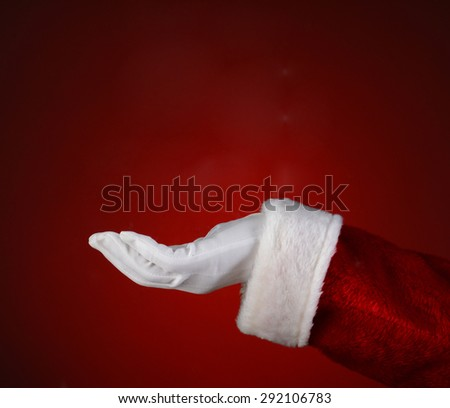 Santa Claus hand with his palm facing up over a light to dark red background. Closeup showing only his hand and arm.