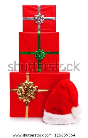 Santa Claus hat and three red gift wrapped Christmas presents with ribbons and bows, isolated on a white background. - stock photo