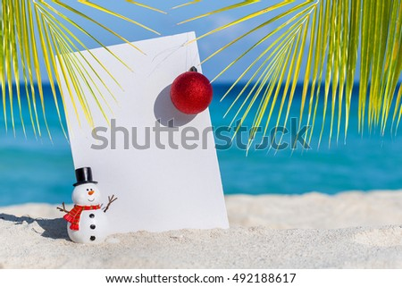 Santa Claus Hat, decoration christmas ball and white blank placard at sandy beach on caribbean sea background