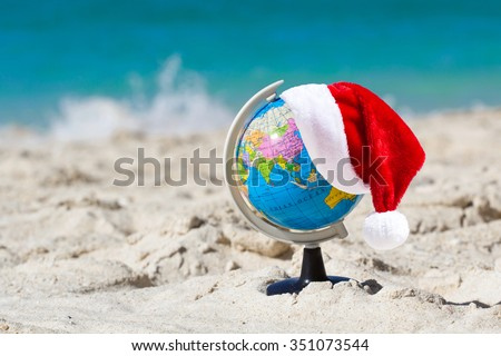 Santa Claus Hat on Globe at tropical beach. Christmas travel concept