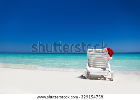 Santa Claus Hat on sunbed near  tropical calm beach with turquoise caribbean sea water and white sand. Christmas vacation concept