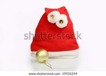 Santa Claus hat with golden christmas tree ball on light background - stock photo