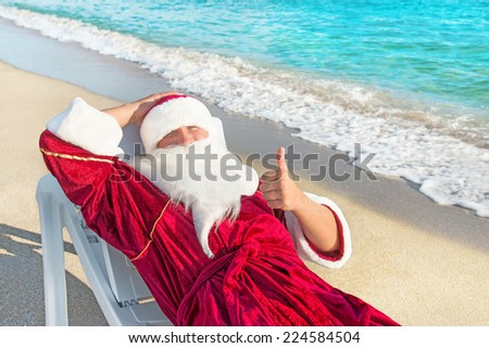 Santa Claus have e rest in chaise longue on sea beach - christmas or happy new year concept - stock photo