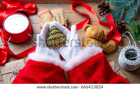 Santa Claus have wrapping a Christmas cookie and other gifts on wooden background