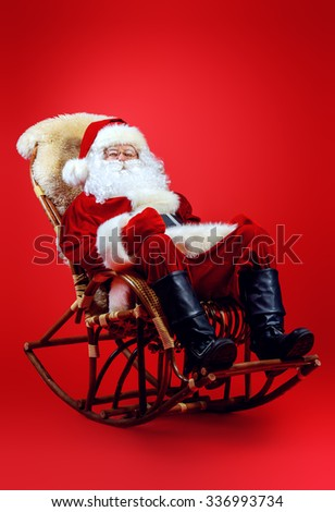Santa Claus having a rest in a rocking chair over red background. Christmas. - stock photo