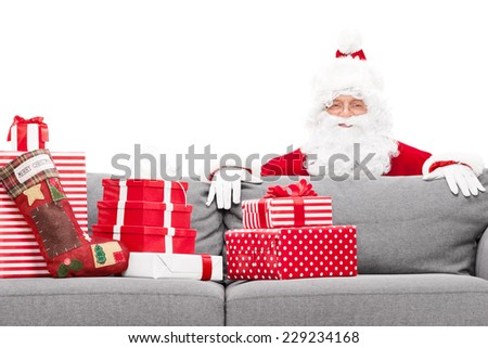 Santa Claus hiding behind a sofa full of Christmas presents isolated against white background - stock photo
