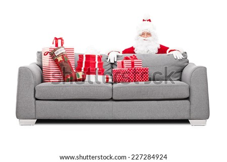 Santa Claus hiding behind a sofa full of Christmas presents isolated on white background - stock photo