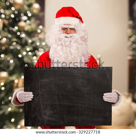 Santa Claus holding a blackboard in his hands - stock photo