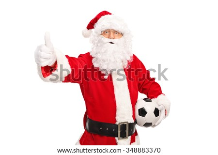 Santa Claus holding a football and giving a thumb up isolated on white background - stock photo