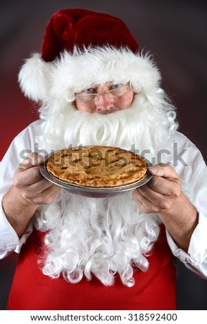 Santa Claus holding a fresh baked apple pie. Santa is wearing a red apron against a light ot dark red background. Vertical format.