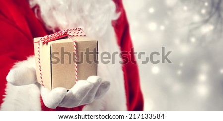 Santa Claus holding a gift in his hand - stock photo