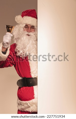 Santa Claus holding a golden bell in his hand while presenting a blank board. - stock photo