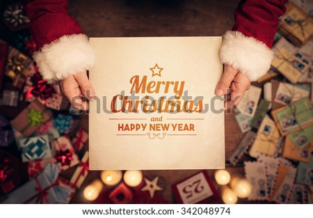 Santa Claus holding a old paper with Merry Christmas and Happy New Year message - stock photo