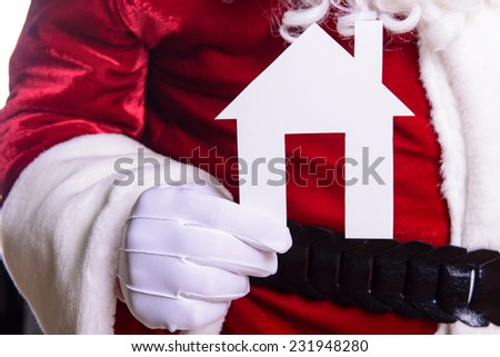 Santa Claus holding a paper house - stock photo