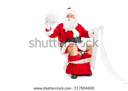Santa Claus holding a pile of shredded paper in one hand and a long blank list in the other seated on a toilet isolated on white background - stock photo