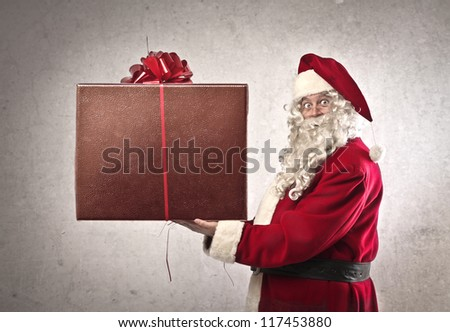 Santa Claus holding a present - stock photo