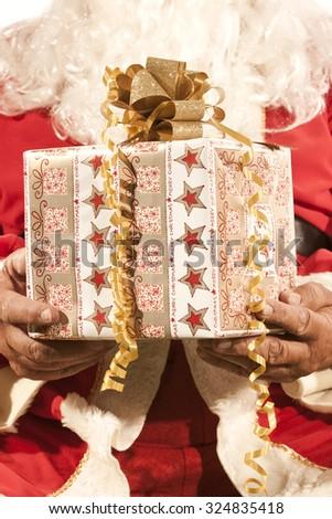 Santa Claus Holding a Present - stock photo