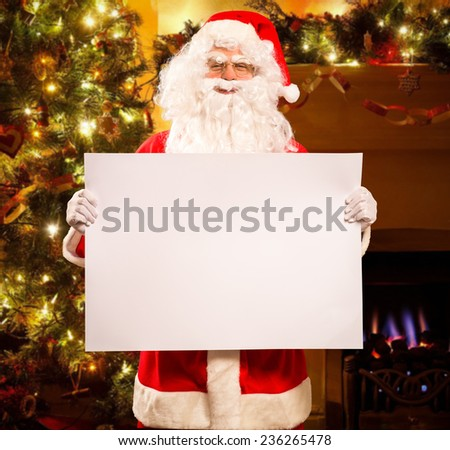 Santa Claus holding a white sign - stock photo