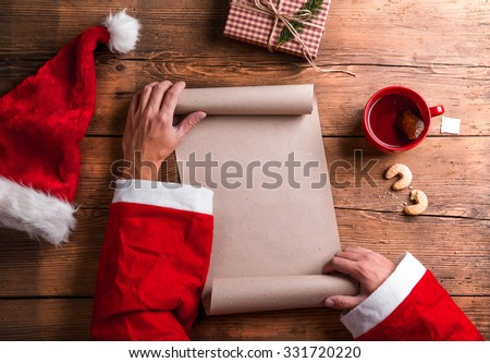 Santa Claus holding an empty wish list in his hands - stock photo