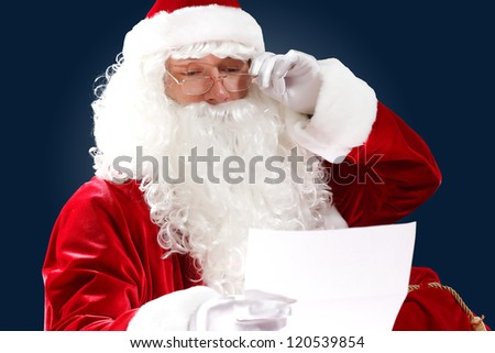 Santa Claus holding and reading a letter to him