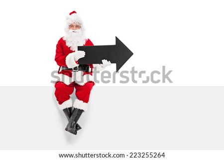 Santa Claus holding black arrow seated on a blank panel isolated on white background - stock photo