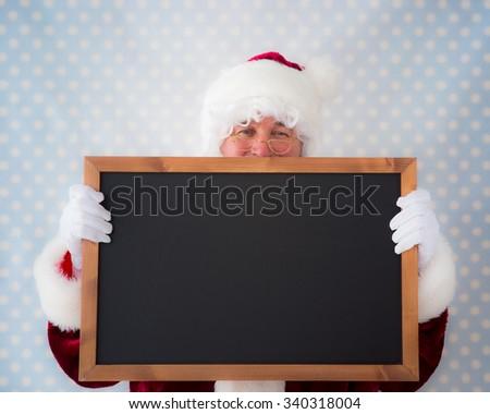 Santa Claus holding blackboard blank. Christmas holiday concept - stock photo