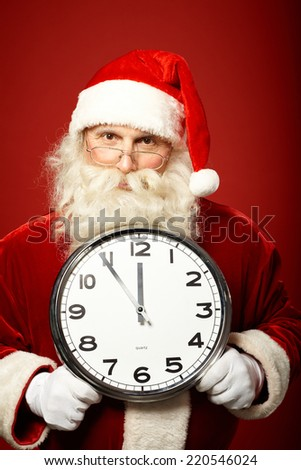 Santa Claus holding clock while warning that xmas is in five minutes - stock photo