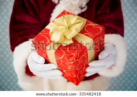 Santa Claus holding gift box in hands. Christmas holiday concept - stock photo
