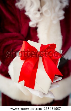 Santa Claus holding gift box in hands. Christmas holiday concept