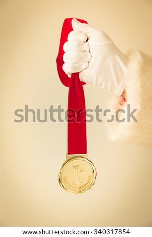 Santa Claus holding gold medal in hands. Christmas holiday concept - stock photo