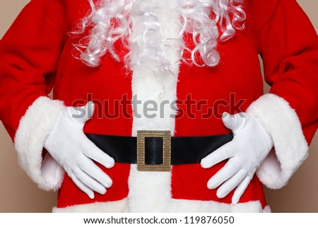 Santa Claus holding his belly, two many cookies I think. - stock photo