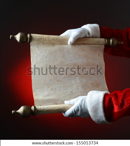 Santa Claus holding his naughty and nice list over a light to dark red background. The list is blank, ready for copy. Only Santa's hands and arms are visible. - stock photo